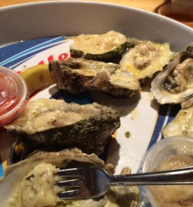 A platter of oysters prepared with garlic sauce and cheese.